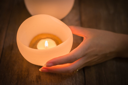 reverent: Candle in young woman hands on wooden background