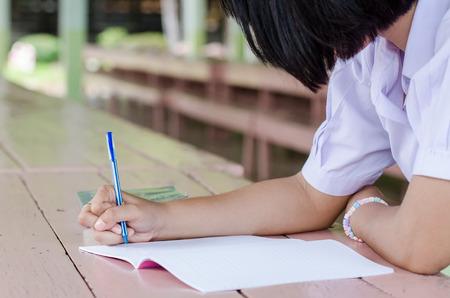 Close up of  young student hands writing on notebook Stock Photo