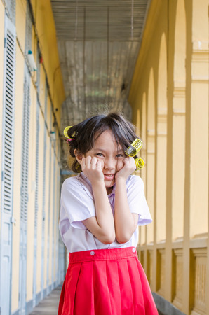 uniform curls: Smiling little schoolgirl in uniform with hair curlers playing at school