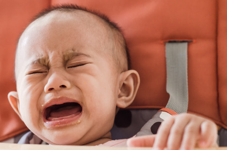 capricious: Asian baby girl sitting in highchair and crying refuses to eat food