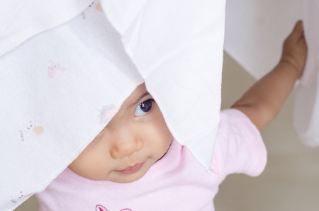 face cloth: Happy little baby girl hidden her face in white cloth diaper Stock Photo