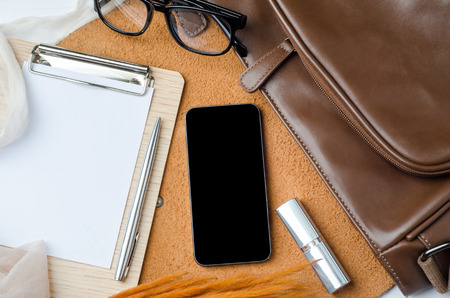 Wooden desktop with smart phone, leather bag, eyeglasses, lipstick, note and pen. Top view of female accessories. Stock Photo
