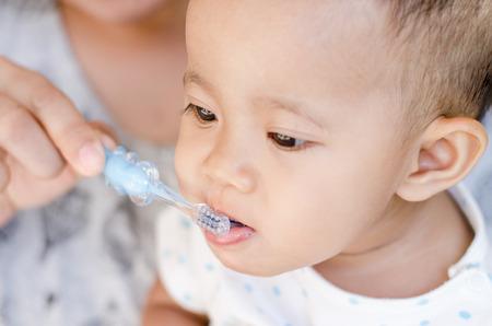 赤ちゃんの女の子の歯磨きを教える母
