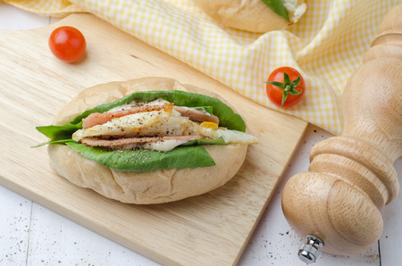 Homemade sandwich with ham, eggs, cheese and vegetables on white wooden table background.