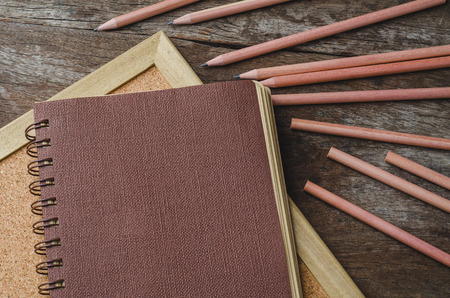 novelist: Brown paper diary with pencils on corkboard and wooden background