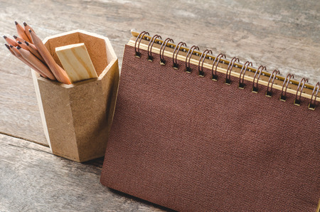 novelist: Brown paper diary with pencils in holder on wooden background