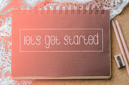 Let's Get Started text on brown notebook with lighting and pencil on corkboard, Business concept.
