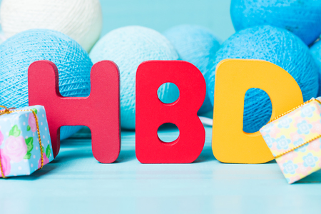 Colorful happy birthday words with garland on blue wooden background