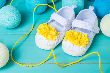 Baby shoes on blue wooden background