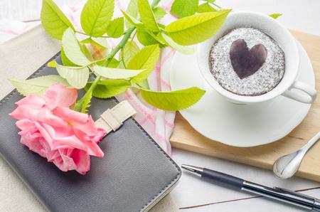 노트북, 펜 및 흰색 나무 배경에 장미 꽃과 컵에 초콜릿 케이크. 흰색 나무 배경에 꽃.