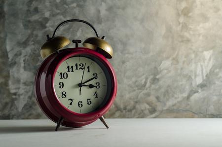 테이블에 복고풍 알람 시계와 함께 베어 시멘트 벽 배경 스톡 콘텐츠