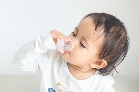 アジアの小さな女の子は自分で薬シロップを取ります