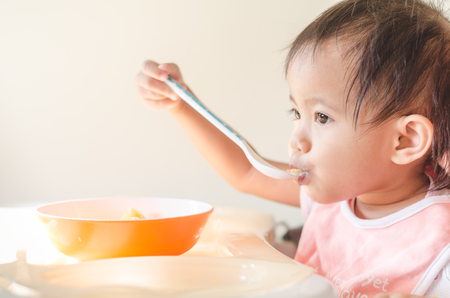Asian toddler girl eating cereals with milk on high chair at home