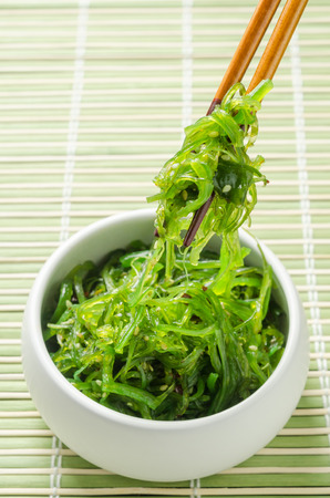 Spicy Seaweed Salad with chopsticks on bamboo background. Stock Photo