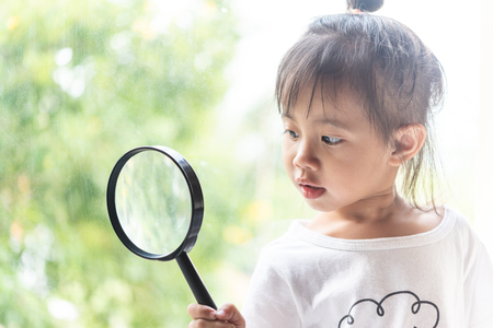 Asian child girl looking with magnifying glass