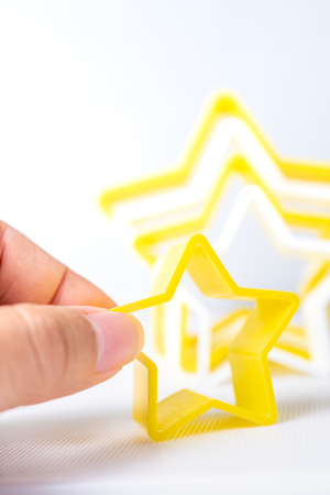 Hand holding star shaped pastry cutter on a white background