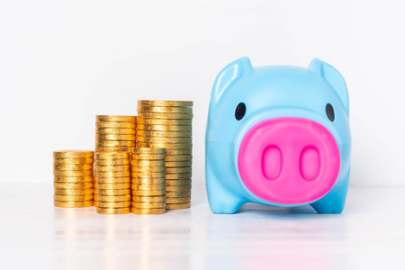 Blue piggy bank with piles of golden coins  on white background. Saving money concept.