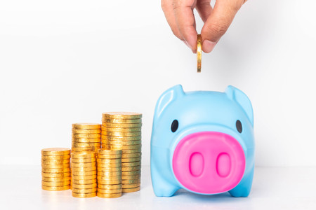 Male hand putting coin into blue piggy bank with piles of golden money on white background. Archivio Fotografico