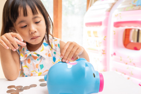 Asian girl putting coin in the piggy bank for saving money. Selective focus of child hand.