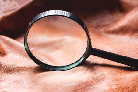 Close up of magnifying glass with leather background. Searching concept. Archivio Fotografico