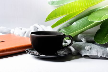 Coffee mug black with notebook and green leaves on wooden table.