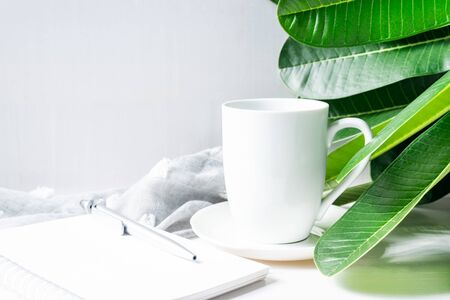 Coffee mug white with green leaves and stationery on wooden table.