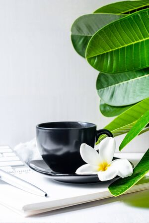 Coffee mug black with flower and leaves on  workspace.