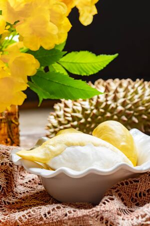 Fresh yellow durian fruit in a bowl and decorate with flowers. Sweet dessert concept.