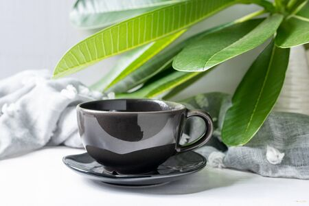 Coffee mug black with leaves on white wooden table Archivio Fotografico