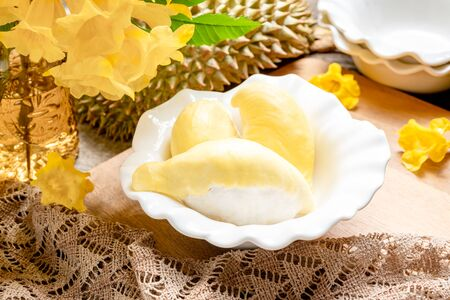 Fresh yellow durian fruit in a bowl and decorate with flowers. Sweet dessert concept