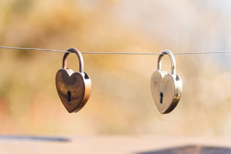 Gold padlocks in the heart shape hanging on rope bridge, Valentines day concept.