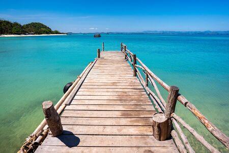 Wooden bridge over crystal clear aqua sea