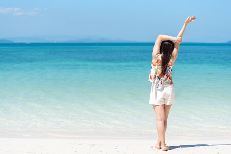 Happy Asian woman relaxing body on white beach with copy space Archivio Fotografico