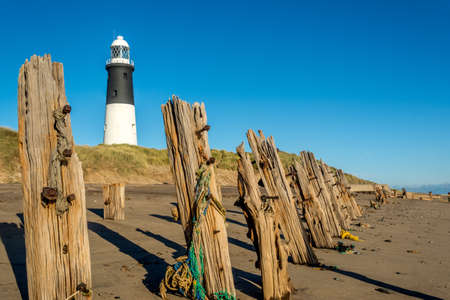 Spurn Point lighthouse and old wooden beach sea defences Stock Photo