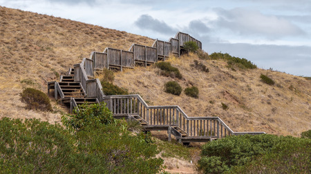 bushwalk: a wooden boardwalk up to the hill surrounded with dry grass