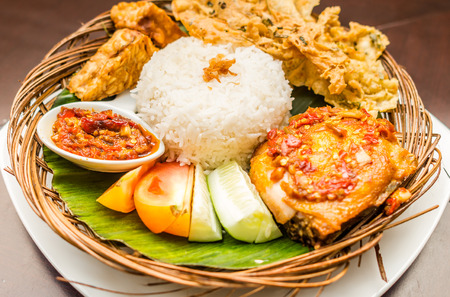 tradisional indonesian cuisine; ayam penyet, fried chicken served with white rice, chili sauce,slices of cucumber, tomato, and chips served on bamboo plaited plate