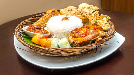 tradisional indonesian cuisine; ayam penyet, fried chicken served with white rice, chili sauce,slices of cucumber, tomato, and chips