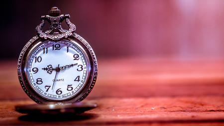 Old and antique pocket watch on wooden floor with blurred background