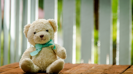 lovely bear rug doll with blue ribbon sitting on the brown wooden desk Stock Photo