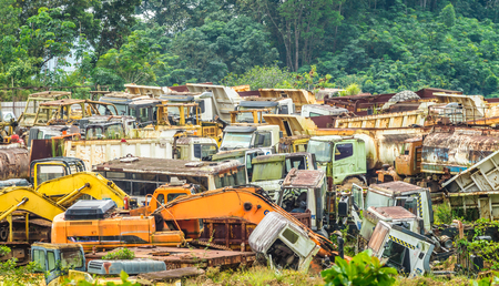 junkyard full of colorful heavy machinery in the valley surrounded by vegetation