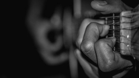 man playing acoustic guitar. selective focus with narrow depth of field