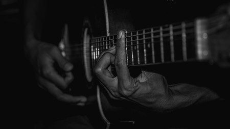 people playing acoustic guitar. selective focus with narrow depth of field