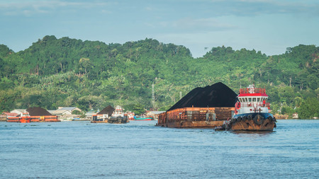 Tugboats pull heavy load barge of black coal in Mahakam river, Borneo, Indonesia