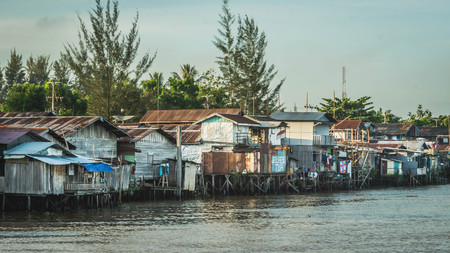 wooden house on the riverbank. slum area over the river. poverty and social problem concept
