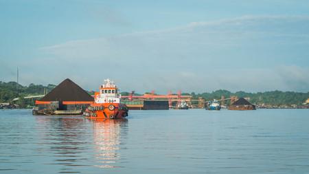 Tugboat pulling heavy loaded barge of black coal in the Mahakam river, Indonesia