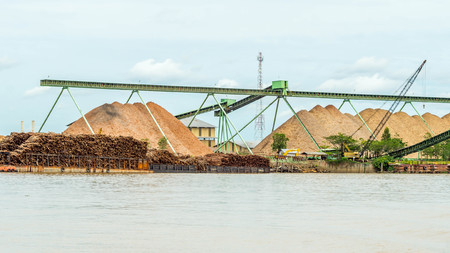 wood chip stockpile / factory on Mahakam riverbank. industrial background