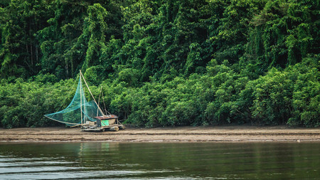 wooden boat with net on the riverbank of Mahakam, Indonesia. traditional fishing method