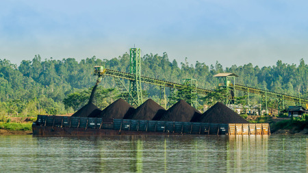 conveyor loading the barge with coal from the stockpile on Mahakam riverbank, Indonesia Standard-Bild
