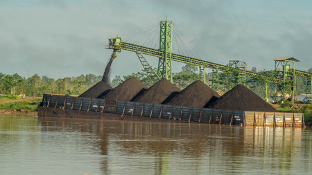 conveyor loading the barge with coal from the stockpile on Mahakam riverbank, Indonesia 免版税图像