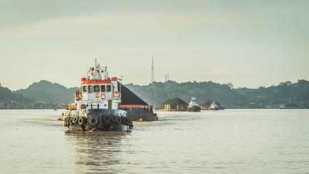 tugboat pull heavy load barge of black coal in Mahakam river, Borneo, Indonesia